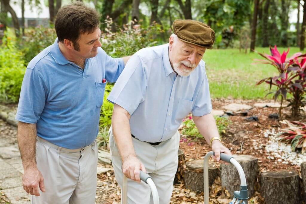 中年人攙扶用輔具走動的老年人